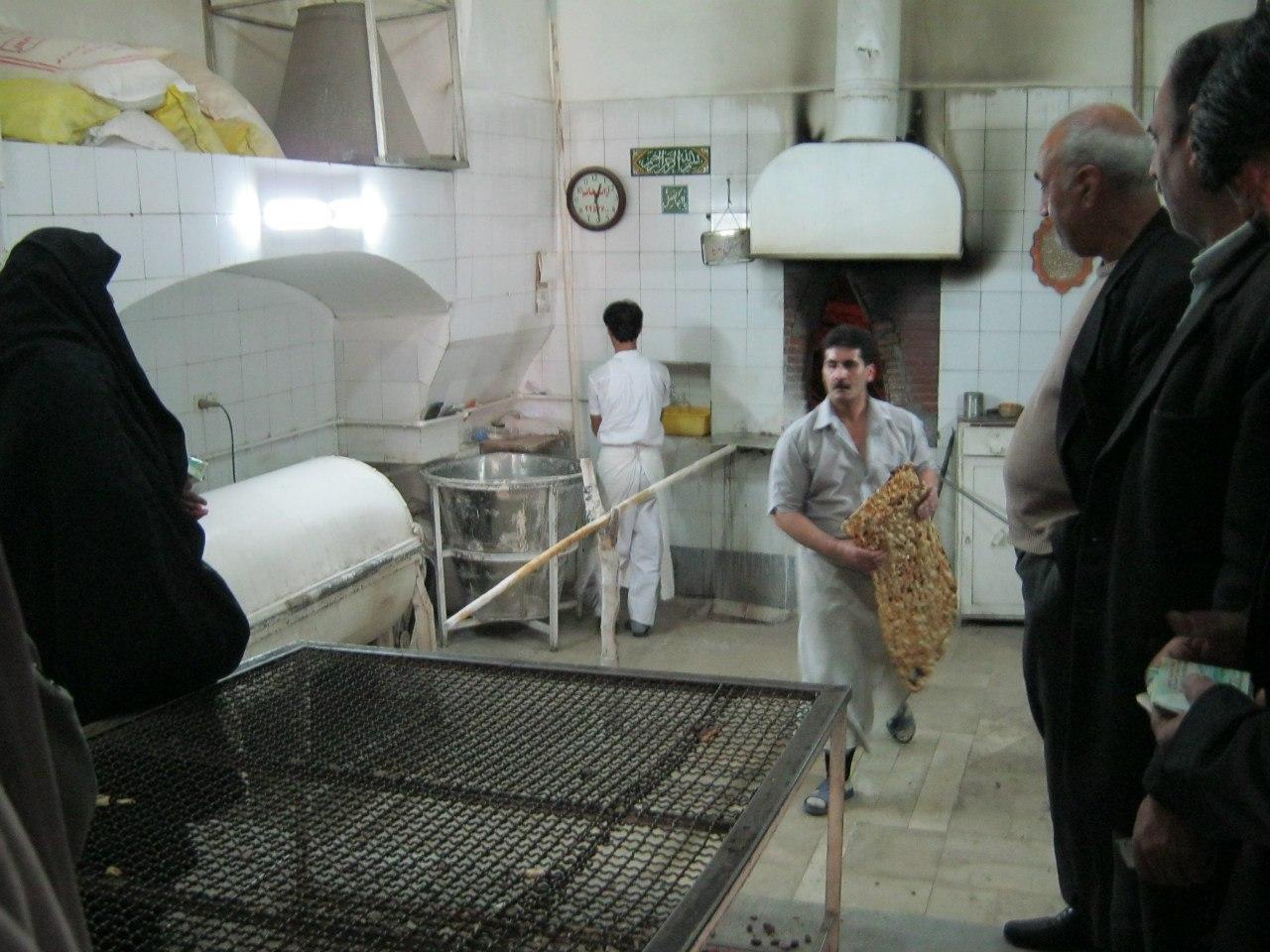 иранская женщина в традиционном чёрном одеянии в пекарне